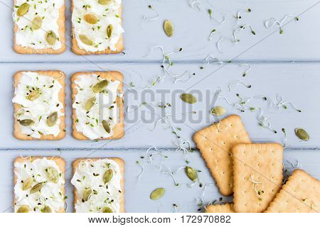 Tasty square crackers with cream cheese pumpkin seeds and micro greens. Appetizers on grey table. Healthy vegetarian snacks top view flat lay