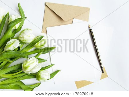 Letter envelope and fresh bouquet on white background. Wedding invitation cards or love letter with white tulips. Romantic or holiday concept top view flat lay overhead view