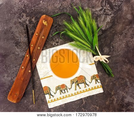 Green herbal tea in a cup incense stick and holder napkin with elephants bright bouquet of spikelets. Oriental composition on dark stone background. Flat lay top view serenity