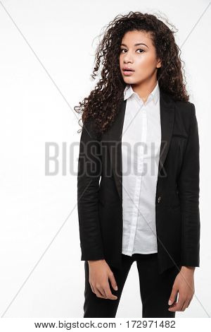 Attractive curly african young businesswoman in suit standing over white background