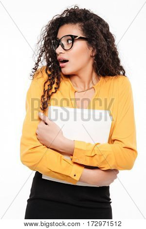 Surprised african young businesswoman holding blank paper and looking away over white background