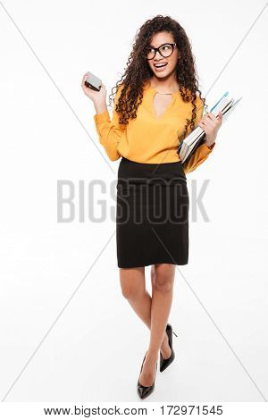 Full length of cheerful african young businesswoman with folders and mobile phone walking over white background