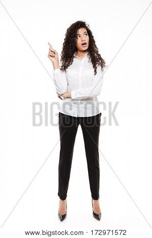 Picture of attractive young curly african lady standing and posing over white background. Looking aside.