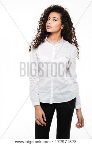 Photo of beautiful young curly african lady standing and posing over white background. Looking at camera.