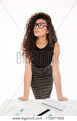 Image of amazing young curly african lady standing over white background near table with documents.