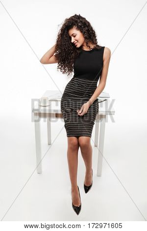 Picture of incredible young curly african lady standing and posing over white background. Looking aside.