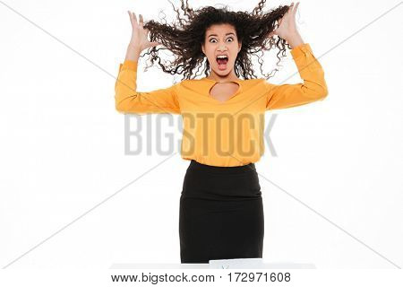 Image of screaming young curly african lady over white background. Looking at camera.