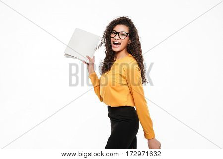Photo of smiling young curly african lady over white background with documents. Looking at camera.