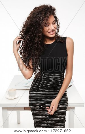 Image of beautiful young curly african lady standing and posing over white background. Looking aside.