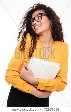 Image of cheerful young curly african woman over white background with documents. Looking aside.