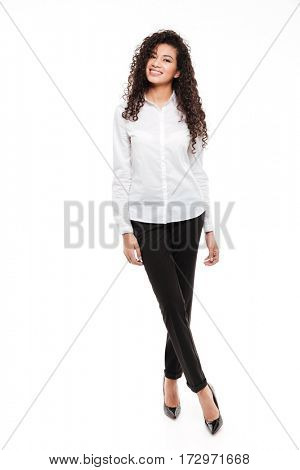 Image of amazing young curly african woman standing and posing over white background. Looking at camera.