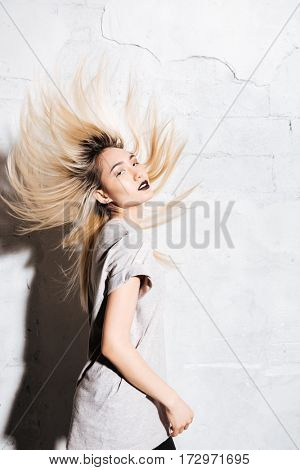 Sensual blonde young woman with black lips dancing and shaking her hair over white background