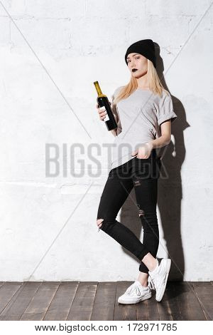 Full length portrait of Hipster girl with bottle of wine which looking at camera with arm at pocket