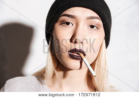 Portrait of beautiful young woman hipster in hat smoking cigarette over white background