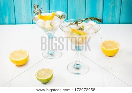 Gin lemon rosemary fizz cocktail with honey and fresh herbs on a white background.