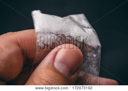 Mans hand holds plastic packet with cocaine powder or another drugs. Macro photo