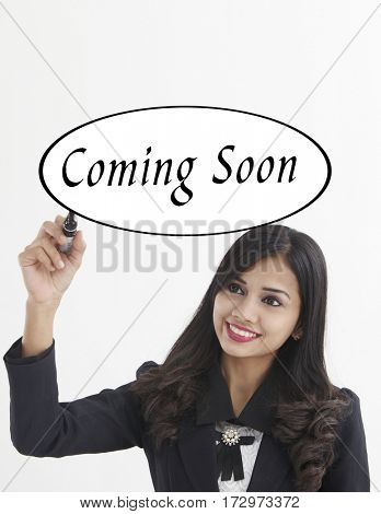 businesswoman holding a marker pen writing -coming soon
