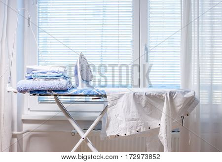 electric iron and shirts in front of window