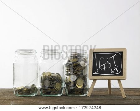 Blackboard with words government service tax and three saving jars from little coins ,half to full.