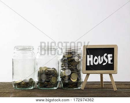 Blackboard with words house and three saving jars from little coins ,half to full.