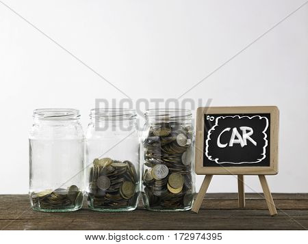 Blackboard with words car and three saving jars from little coins ,half to full.