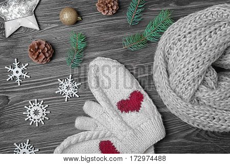 Knitted scarf, mittens and Christmas decor on wooden background