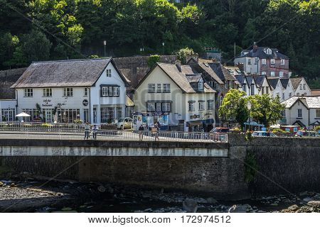 Lynmouth Devon England 13 July 2016: The bridge across the river across the West lyn. People walk by the bridge. Many houses. Cafes and small shops.