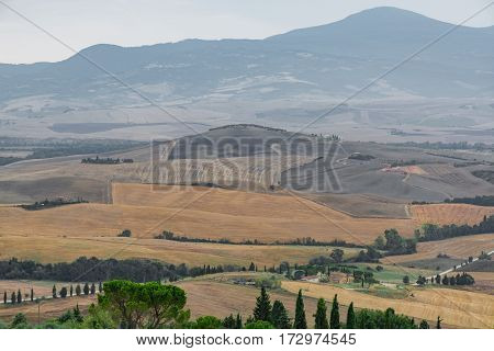 Hills and harvested fields and blue sky in Tuscany Italy