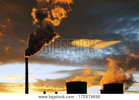 industrial view. golden smoke from factory during sunset