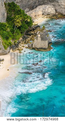 Rock in the ocean with beautiful palms behind at Atuh beach on Nusa Penida island, Indonesia.