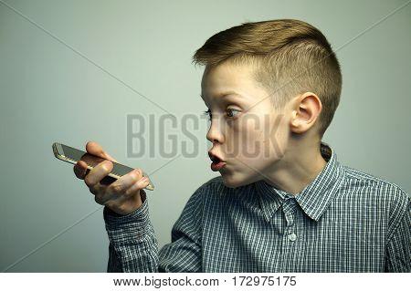 Portrait of a serious angry teenage boy talking on smartphone softbox lighting studio shot.