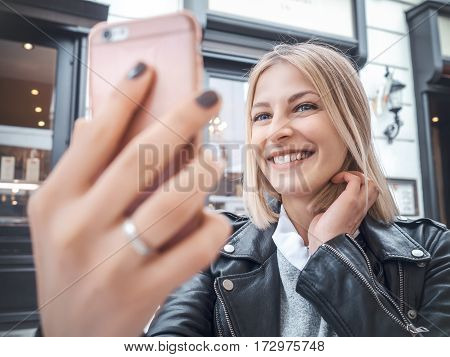 Smiling young woman making a selfie outdoors