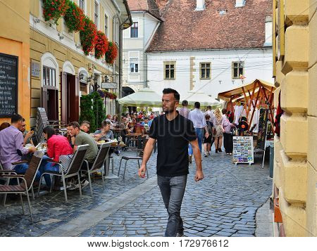CLUJ-NAPOCA ROMANIA - JUNE 10 2016: People walk on a narrow street with outdoor restaurant cafe and artisans' stands in historical center. Turists have lunch at outdoor terrace and buy souvenirs. Tourists visit and have lounch at outdoor restaurant cafe o
