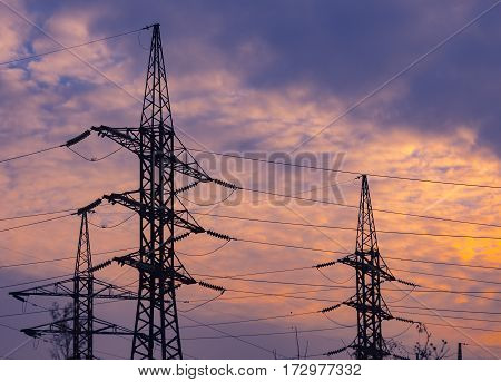 Metal construction of electricity lines on the background of orange sky, bottom view