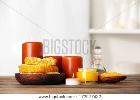 Spa concept. Honey treatments, candles and aroma oil on wooden table