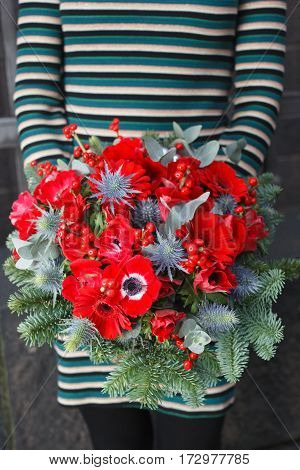Red bouquet with anemone, ilex and daisy gerber flowers
