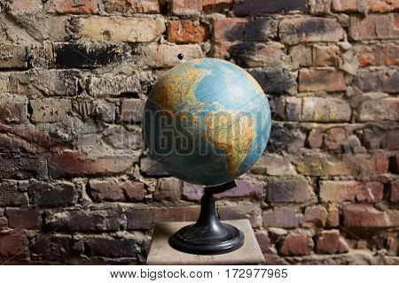 Spinning Globe. Earth globe on a brick wall background.