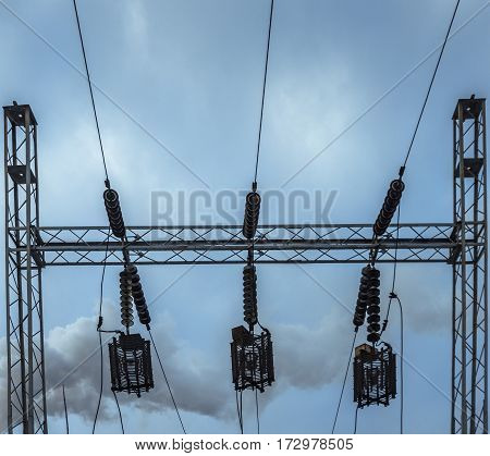 Metal construction of electricity lines on the background of deep blue sky, bottom view