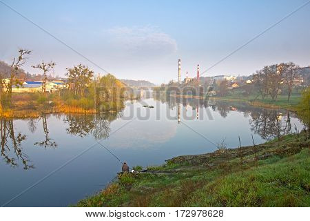 Man catch the fish near factory at river dam in sunrise