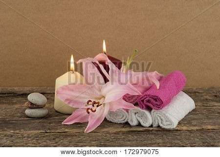 Beautiful composition with two candles, stack of spa stones, pink lily and towels on wooden background, spa treatment concept