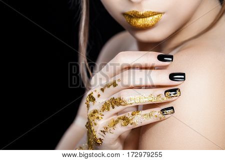 Beautiful Fashion woman model face portrait with gold lipstick and black nails. Glamour girl with bright makeup. Beauty female. Perfect skin and make up. Nail polish. Isolated on black