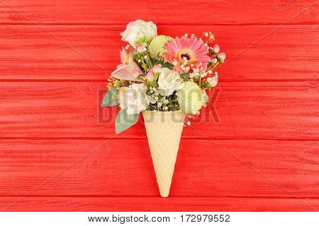 Waffle cone with composition of beautiful flowers on red background