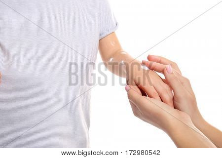 Woman applying cream onto skin of child ill with chickenpox, on white background