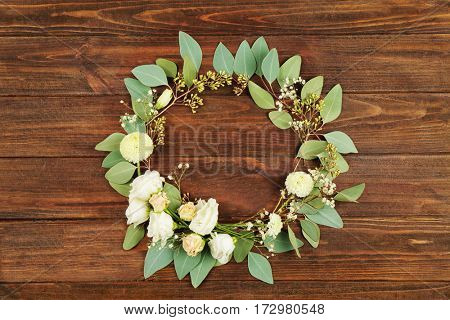 Floral wreath frame on wooden background