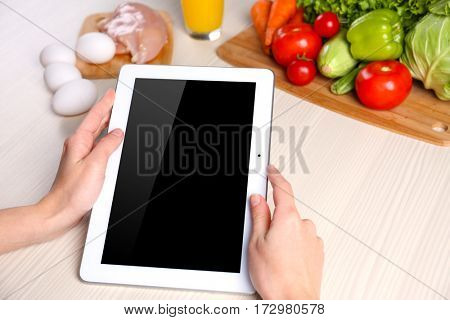 Woman with tablet and ingredients on kitchen table