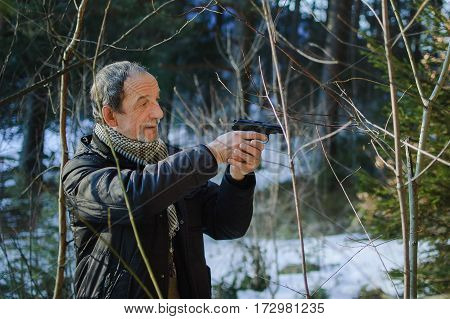 An elderly man with a gun in the woods in early spring. Man dressed in a black jacket and scarf. He holds the gun in both hands and aiming into the distance