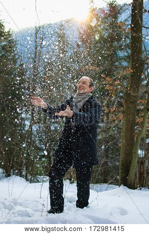 The spring portrait in full growth of elderly man with a gray beard. The man smiles on the background of the forest in early spring. He throws up the snow and smiling,