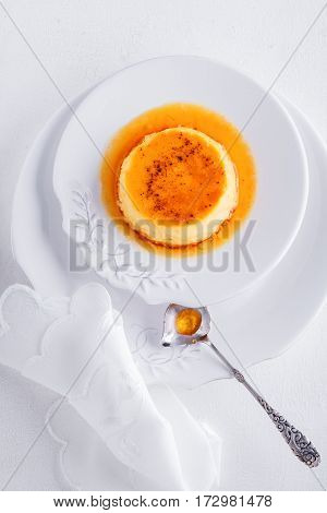 Creme Caramel on a plate served on a table.