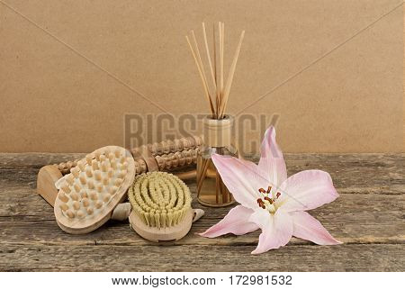 Beautiful composition with aromatic oil and massage brushes on wooden background, weight loss and body care concept