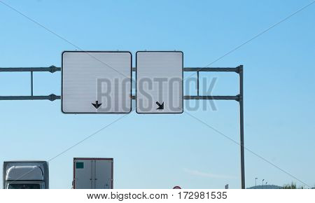 Two blank highway signs, each has arrow pointing different direction, where to go,  insert your text, tops of 2 transport trucks, each going opposite direction.  Blank space, message space.